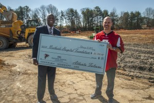Atlanta Falcons players Matt Bryant and D.J. Shockley present a $30,000 check to Northside Hospital during the East Cobb Medical Center groundbreaking to support the onocology program.