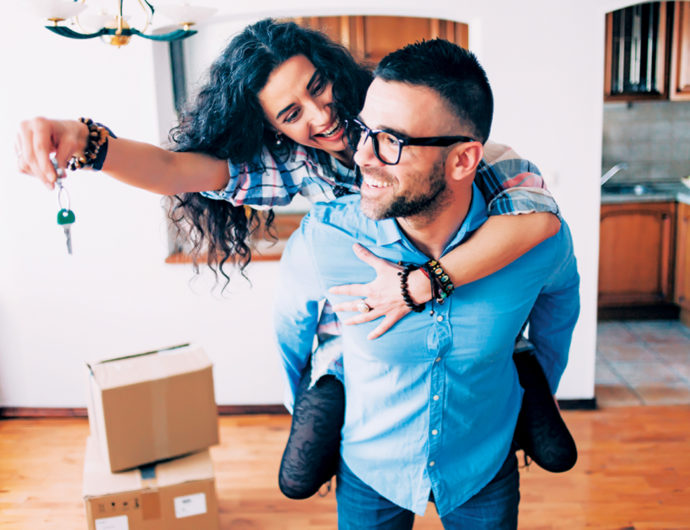 Young couple holding the keys for their new home.